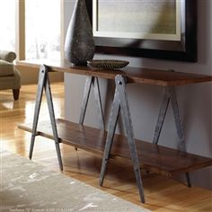 Pictured is the Charleston Forge manufactured Sawhorse 70-in Industrial Console Table that measures 70-in x 17.5-in x 31-in with custom iron finishes and table top options to choose from.