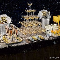 A glammed-out silver and gold party table. A champagne tower, trays of elegant beverages, silver ice buckets and coordinating metallic-colored treats are full of sophisticated cheer. Shimmery blue floral sheeting makes the perfect backdrop for your silver and gold table to pop. Add the finishing touch to this classy spread with a table skirt made from gold metallic fringe and a boa tinsel garland.