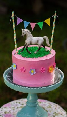 Horse themed rainbow cake with four colourful layers inside. Comes with Schleich horse and bunting.