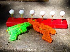 #Pongpongballen spuiten. Maak wat gaten in een houten balk, steek er #golf tees in en probeer met waterpistolen de pingpongballen eraf te schieten. (www.opvoedproducten.nl)