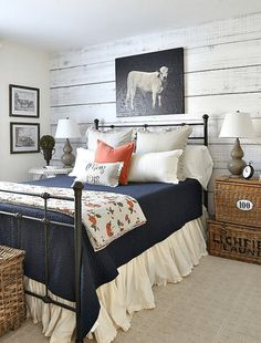 country style bedroom with orange accents, quilt with burnt orange flowers, white shiplap, black cow wall art, navy blanket, wrought iron bed, blood orange, burnt orange, reddish-orange, tangerine orange, pantone autumn maple