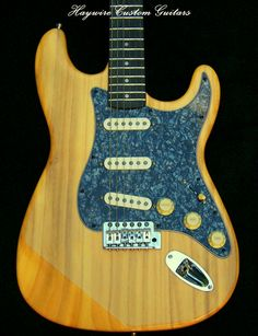 """This Haywire Custom Guitars custom guitar includes: Light Swamp Ash Strat body, Mojotone """"58 Quiet Coil w/Hot Bridge"""" Strat® Pickup Set with black covers and .022 paper & oil cap-""""Vitamin"""" series, Maple/Rosewood fret board neck 12"""" radius with 6105 frets and 43mm nut width, Charcoal Black Pearl pick guard with Cream Pickup covers + Knobs Locking tuners with all chrome hardware"""