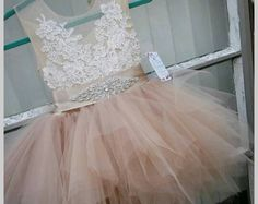 Glamorous...stunning and precious! Yet another stunner! This summer add a little glamour to the little one.  Our stunning flower girl dress with champagne blush tutu skirt and rhinestone belt will makes every little one shines, sparkle and twinkle like a star...  The bodice is made of tan/ nude see through English net , french lace and tutu length skirt of champagne blush (tan) tulle. The skirt length is above the knee.  Delicate pearl buttons closure and sheer back give an elegant finis...