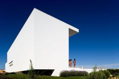 This house, located in the touristic complex of Martinhal, in Portugal, was designed by the Lisbon-based architectural studio ARX Portugal. It has large windows that allow for much natural light to enter the home, which is then reflected on crisp white walls and floors, illuminating the entire home