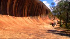 A wave of rock shaped by wind and rain towers above a plain in a travelers tales australias spectacular rock formationswave rock near hyden western australia publicscrutiny Gallery