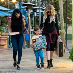 Walk this way: Auntie Khloe put a protective hand on her little nephew