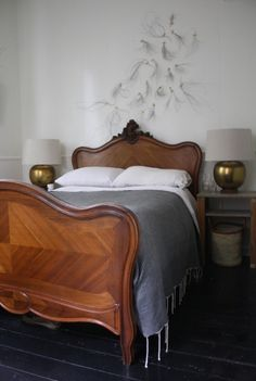 what a bed! love the art above the headboard too and those golden globe lamps!