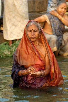 Indian woman worships in the Ganges River at Varanasi, a sacred site for Hindus.