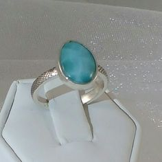 Lovely Larimar Gemstone Ring Beautiful blue larimar size 7 sterling silver ring.  The10x14mm oval larimar cabochon stone is bezel set and originates from the Dominican Republic. New.  Measurements are approximate. Photos may be enlarged to show detail. Jewelry Rings