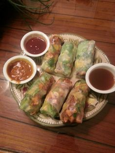 Asian spring rolls with mixed greens, mint, cilantro, shredded carrots, oranges, tofu and sesame seeds with  thai peanut sauce, sweet & sour sauce and sesame ginger sauce