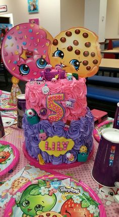 2 tier shopkins cake. Top tier rainbow chip. Bottom tier chocolate and cherry chip. Vanilla buttercream rosettes and toy shopkins for decoration.