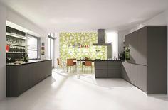 Die Oberflächen der grifflosen Küche mit hochwertiger Beschichtung aus Melamin sind funktionell und edel zugleich. Der weiße Boden fängt das markante Steingrau der Küchenfront auf und harmoniert zugleich mit der weiß-grün gemusterten Tapete hinter dem Essbereich. So wird das Stimmungsbild etwas aufgelockert und Frische versprüht. Schickes Detail sind auch die Regalboarde mit indirekter Beleuchtung.