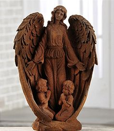 Beautiful angel statue with two young children at her feet. In a rust color with a sandy finish.