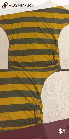 Eye candy gray and mustard striped dolman tee Grey and mustard striped dolman tee. It has drawstring ties on both sides of the shirt. It's super cute but doesn't fit me anymore.  It is a size large but runs more like a medium. Tops Tees - Short Sleeve