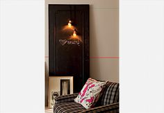 De uma porta sem uso no apartamento, Marcio Mota fez um quadro de avisos na sala. Depois de pintá-la com tinta de lousa, ele pendurou os fios com as duas lâmpadas douradas espelhadas