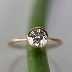 A stunning 6mm Charles & Colvard Moissanite in a warm rose gold setting. Framed in a sleek lower tapered bezel, this scintillating stone throws fire at every angle. Its unbelievable brilliance surpasses that of a diamond. A classic, timeless piece that makes a statement. Moissanite is