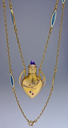 An Antique Jeweled Gold Perfume Flask (Scent Bottle) Pendant Necklace  The perfume flask is shaped as an amphora with Art Nouveau handles and gem-set engraved decorations.  The cap is set with a cabochon amethyst.   The gold chain with six double-sided inserts of blue guilloche and white opaque enamel.  Made by Russian firm of Feodor Lorie, a prominent Moscow jeweler, between 1908 and 1917.
