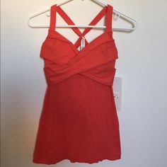 Lululemon Wrap It Up Tank Lululemon 'Wrap It Up' tank top in vibrant coral/red, size 4. New with tags!!! Luxtreme 4-way stretch fabric. Lightweight mesh body with Coolmax moisture-wicking liner. Racerback style with light support and removeable bra cups. Wish this fit me better. Perfect gift for yourself or someone special! lululemon athletica Tops Tank Tops