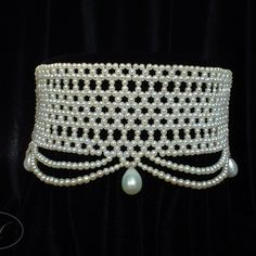 Dramatically wide white woven seed pearl choker with graduated pearl drapes and large pearl drop beads. Inspired by Le Belle Époque Fashions. Most pieces available for purchase can be adjusted to suit a clients needs. If you are interested in custom lengths or custom orders utilizing alternative metals, gems or beading styles please don't hesitate to contact me.