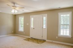 Spacious and neutral living room with light carpeting and several windows ©Balducci Builders