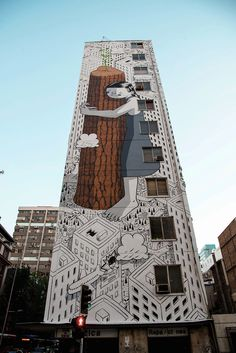 Italian artist Francesco Camillo Giogino, orMillo (previously here and here), has painted his latest sky-high mural in the heart of Chile. Never Give Up, created in his signature cartoonish style, features a female figure in the forefront clutching the trunk of a tree. The city behind the girl is b