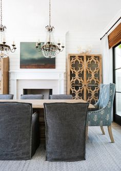 Gorgeous, inviting dining room with shiplap walls, fireplace, and crystal chandeliers | Blackband Design