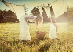 mother and daughter hanging laundry on a clothesline