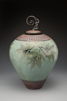 """""""Curlyknob Urn"""" by Suzanne Crane. Flora from the Blue Ridge Mountains imprints a wheel-thrown stoneware urn with twined finial. Glazed in green, with black trim and red iron oxide on the hand-stamped border. Ceramic Boxes, Glass Ceramic, Ceramic Clay, Ceramic Pottery, Pottery Art, Ceramic Jars, Kintsugi, Earthenware, Stoneware"""