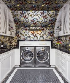 Butterfly wallpaper in playful laundry room with chrome washer and dryer and white cabinetry