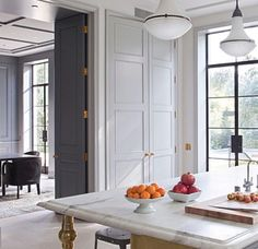 Elegant kitchen with brass detailing, marble, steel framed doors and windows and detailed joinery and ceiling mouldings.