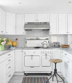 The homeowner kept the kitchen's old Chambers stove and cabinets—now improved with new fronts and a coat of Benjamin Moore's Patriotic White—but jettisoned the Formica counters and dark backsplash in favor of marble and white subway tiles. A Design Workshop stool from ABC Carpet & Home and a Dash & Albert rug decorate the kitchen.   - CountryLiving.com