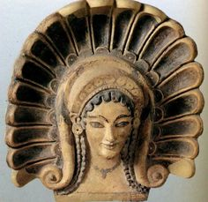 19 rays behind the hair. The hair looks like Hathor, Egypt. Etruscan terracotta antefix (roofing tile)