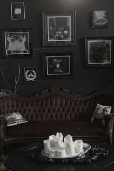 dark walls + tufted antique sofa + candles + gallery wall + victorian