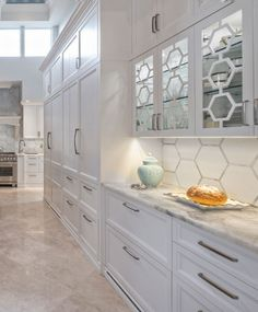 How to make the classic white #kitchen unique? These hexagon glass panels are fun and different. They are highly decorative and display your stored glassware. #kitchens #kitchencabinetry #whitekitchen #whitekitchencabinetry #hexagonglasspanels #hexagoninkitchen #kitchendesign #kitchenideas #kitcheninspiration #panelreadyrefrigerators #kitchendisplay #kitchenstorage Kitchen Display, Kitchen Storage, Mudroom Laundry Room, Bathroom Cabinetry, All White Kitchen, Classic White, Glass Panels, Space Saving, Kitchen Remodel