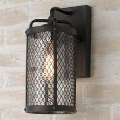 """The rough hewn character of the metallic matte black gilded mesh shade reveals its softer side when radiating golden light shimmers through the water glass cylinder, it feels as if these outdoor lights were forged in an iron shop. (12.9""""Hx6""""Wx7.6""""D)60W max medium base socket.Backplate: 8.4""""Hx4.75""""WTop to outlet: 4.25"""""""