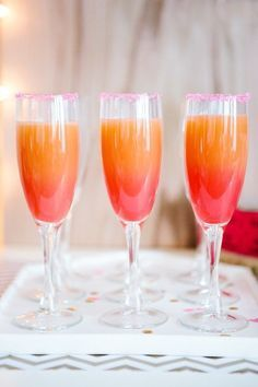 Greet your guests at the door with a stunning signature cocktail. This ombre champagne cocktail in sunset hues features bright pink sugar along the flute's rim and zesty grapefruit flavor.