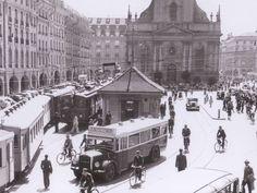 Bern Bahnhof Schwarz-weiss-Bild: Im Hintergrund eine Kirche, vordran ein Postauto, links davon ein Zug, rechts davon Velofahrer und Fussgänger