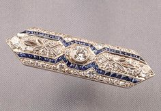 Art Deco Platinum, Sapphire, and Diamond Brooch, bezel-set with an old European-cut diamond, and set throughout with old European and old single-cut diamonds, approx. total wt. 2.12 cts., calibre-cut sapphire highlights, millegrain accents, lg. 1 7/8 in.