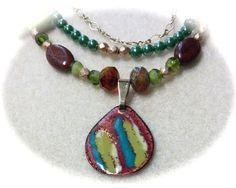 Twisting Vines by Finales on Etsy  Enamel on copper pendant drops from three strands of matching beads, and a gold vine link... Exquisite work of craftsmanship!  Materials: beads, greens, reds, blues, pendant, enamel, three strand  $55.00
