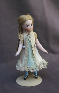 """Rare model of 4"""" pocket doll, with an unusual bru lookalike face and blue socks.     She as a swivel head with cobalt blue inset glass eyes and a tiny closed mouth. Stunning almond-shaped eyes with accentuated corners, long eyelashes and single stroke brows. Original wig with two braids, in beautiful condition, I can't say if it's natural hair or mohair."""