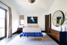 "In a guest bedroom, a KGBL bench upholstered in a bold Métaphores fabric ties into the colors of ""X-Ray Heel"" by Tyler Shields above the custom bed 