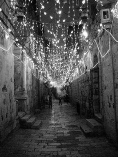 black and white street photography | Cobbled street adorned with lights
