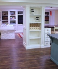For a basement or other room where load-bearing poles/columns are necessary: build shelves around them - could even connect them by a desk or buffet area (which is what it looks like in this pin image).  Cute, functional, and separates the areas.