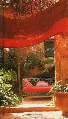 Strong summery color - like a vacation warm ochre courtyard and jungle plants shade sail cloth in rich umber and charming wrought iron green painted day bed