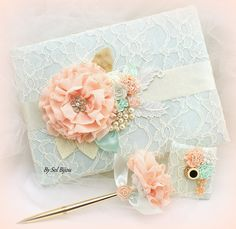 ***Made Upon Request- This listing is for a guestbook, pen base and pen. The set can be made in ANY color scheme    This is an elegant combination of elegant and feminine tones: ivory, gold, coral and mint green. Made only with the finest of materials and with extreme attention to detail, this vintage-inspired bridal guest book and pen set has been covered in ivory lace over mint fabric. Decorated with my exquisite handmade flowers, sparkly crystal jewels and my signature cluster of pearls…