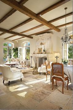 French Country Great Room & Dining. Love the wood beam ceiling, stone fireplace & stone flooring.