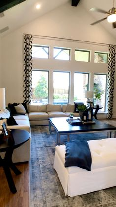 Large Living room with vaulted ceiling, open to the dual-tone white kitchen cabinets with dark lowers. Black and White makes a bold decorating statement! Click to see more photos of model home tours....video by THE DECORATING COACH... #decoratingideas #livingroomdecor #whitekitchen #openconcept #blackandwhitedecor