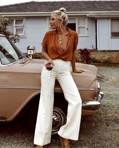 desert style, light materials, flow burnt orange blouse, high waist creamy white pants gold necklace bohemian