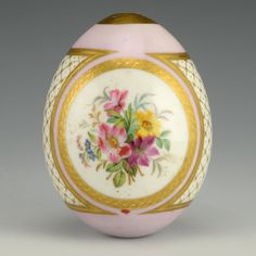 A Russian porcelain Easter egg, circa 1900. The front and back of the pink ground egg decorated with vibrant floral sprays against a white ground within a circular gilded border cartouche, the sides decorated with gilded lattice work against a white ground.