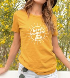 $22 - These womens graphic tees are inspired by the Beatles and 70s retro style. This graphic tee is made of  soft, lightweight fabric and has a modern fit. Great for everyday, festivals, or workouts. Check out the heather colors that have a bit of added polyester for some extra drape. Here comes the sun!